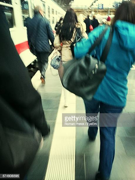 rear view of people walking on railroad station platform - roman pretot stock-fotos und bilder