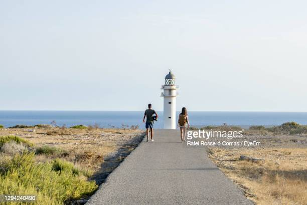 rear view of people walking on sea shore against sky - islas baleares fotografías e imágenes de stock