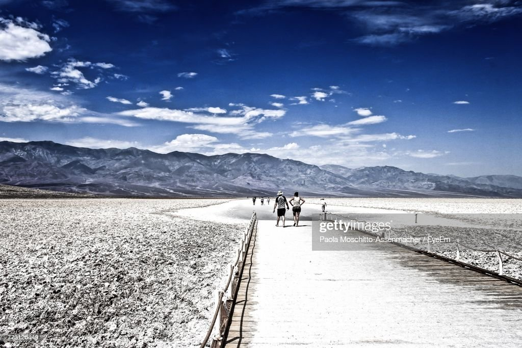 Rear View Of People Walking On Snow Covered Land Against Sky : Photo