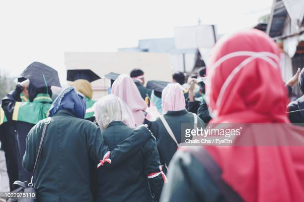 rear view of people walking on street - graduation crowd stock pictures, royalty-free photos & images