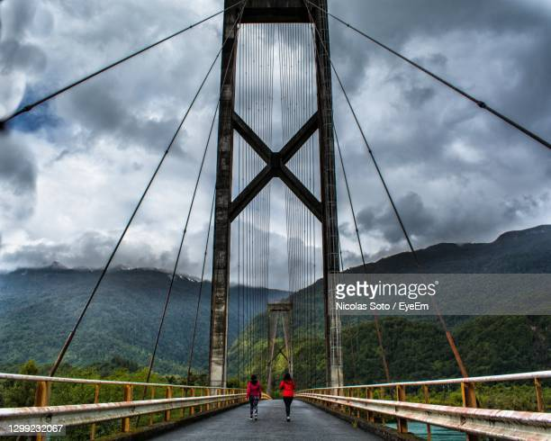 rear view of people walking on suspension bridge against sky - symmetry stock pictures, royalty-free photos & images