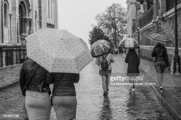 Rear View Of People Walking On Wet Road During Rain