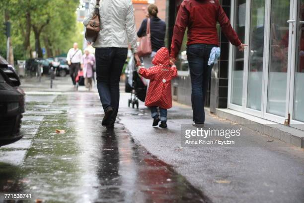 rear view of people walking on wet road - low section stock pictures, royalty-free photos & images
