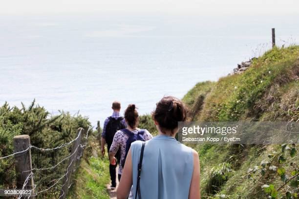 rear view of people walking towards sea on field against sky - county cork stock pictures, royalty-free photos & images