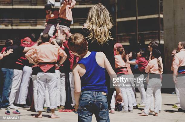Rear View Of People Watching Castellers Forming Human Pyramid