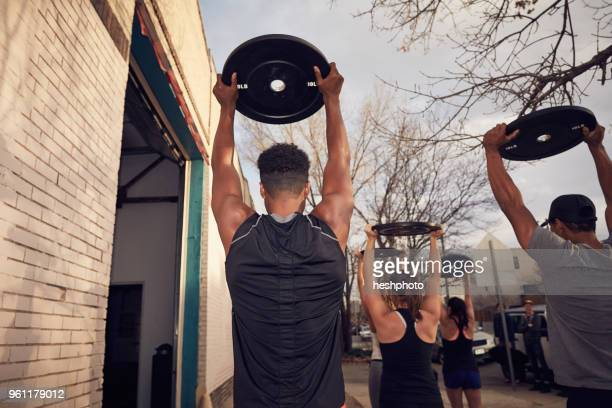 rear view of people with arms raised carrying weights equipment - heshphoto stockfoto's en -beelden