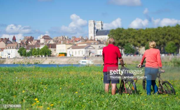 rear view of people with bicycles on grassy field against sky - シャロンシュルソーヌ ストックフォトと画像