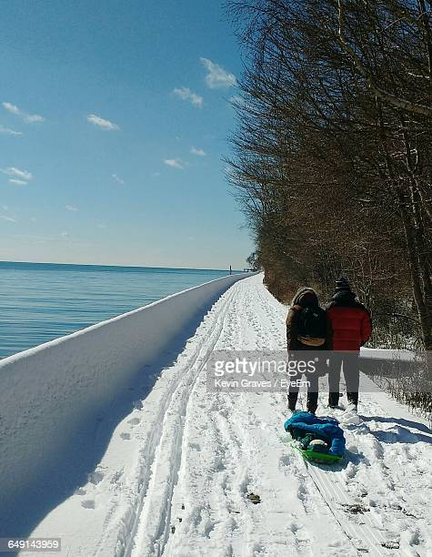 rear view of people with sled on snow covered lakeshore - tobogganing stock pictures, royalty-free photos & images