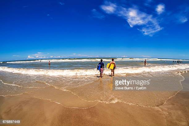 rear view of people with surfboards walking at beach against blue sky on sunny day - cocoa beach stock pictures, royalty-free photos & images
