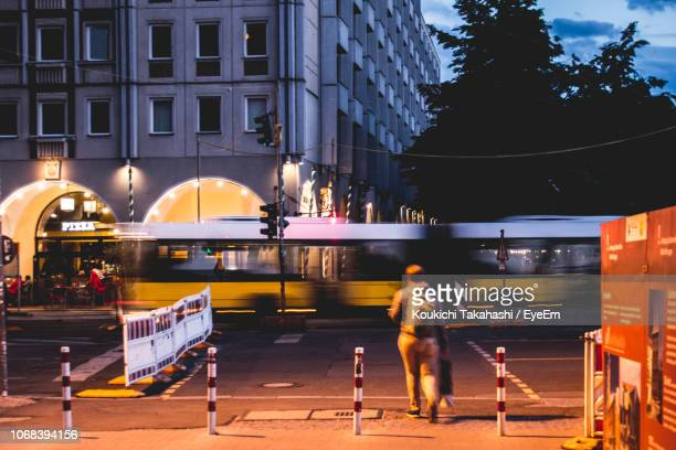 Rear View Of Person Crossing Road In City At Dusk