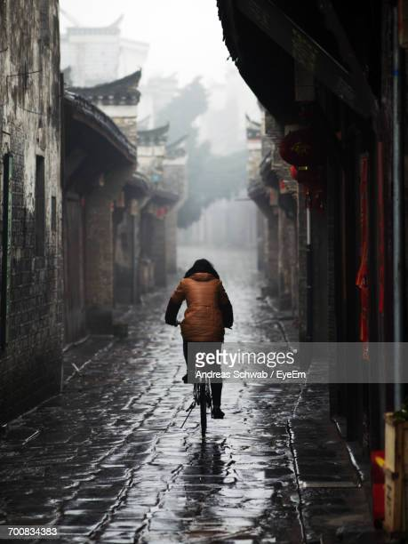 Rear View Of Person Cycling On Wet Road During Rainy Season
