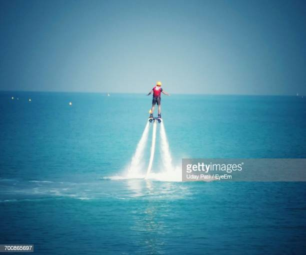 Rear View Of Person Flyboarding At Sea Against Blue Sky