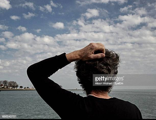 Rear View Of Person Hand On Head Against River And Cloudy Sky