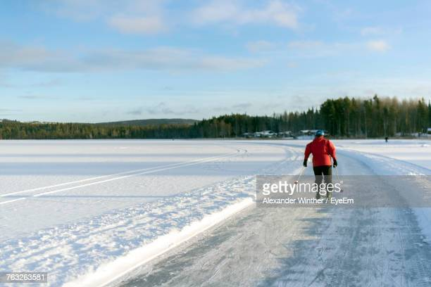 rear view of person ice skating on snow covered road - レクサンド ストックフォトと画像