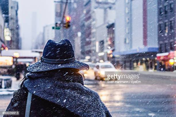 Rear View Of Person In Hat Walking In City During Snowfall