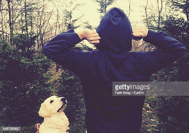 Rear View Of Person In Hooded Shirt With Dog At Forest