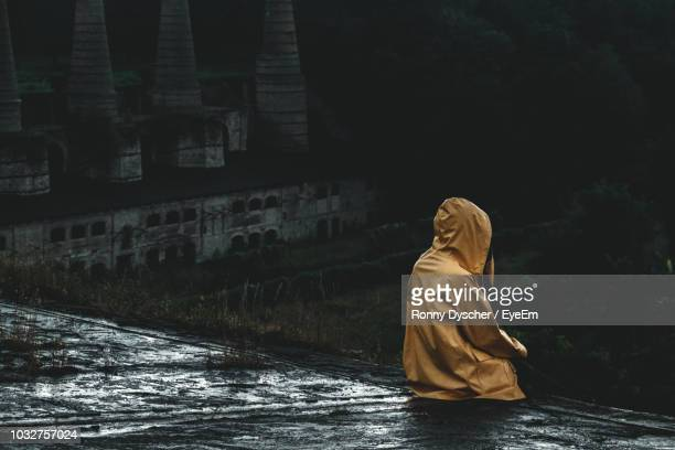 rear view of person in raincoat sitting on rooftop - suicide stock pictures, royalty-free photos & images