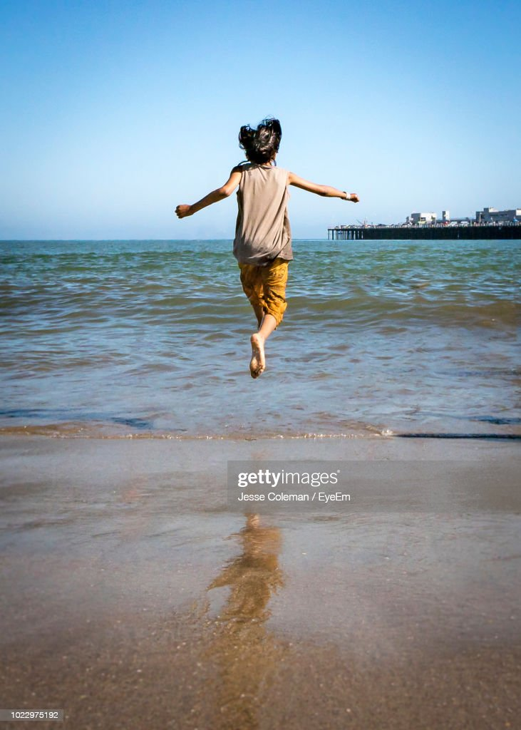 Rear View Of Person Jumping On Beach : Stock Photo