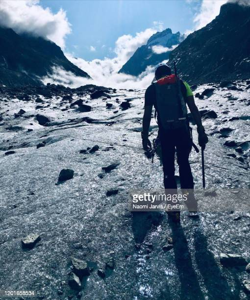rear view of person on snowcapped mountain - naomi jarvis stock pictures, royalty-free photos & images