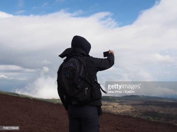 Rear View Of Person Photographing With Mobile Phone While Standing On Field Against Cloudy Sky