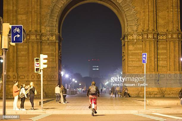 Rear View Of Person Riding Bicycle On Street At Night