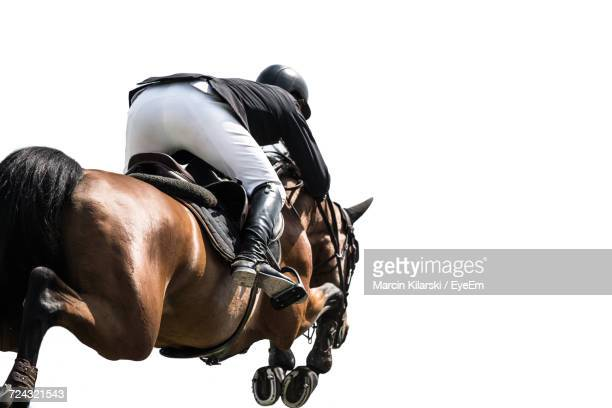 Rear View Of Person Riding Horse In Competition