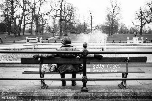 Rear View Of Person Sitting On Bench At Park