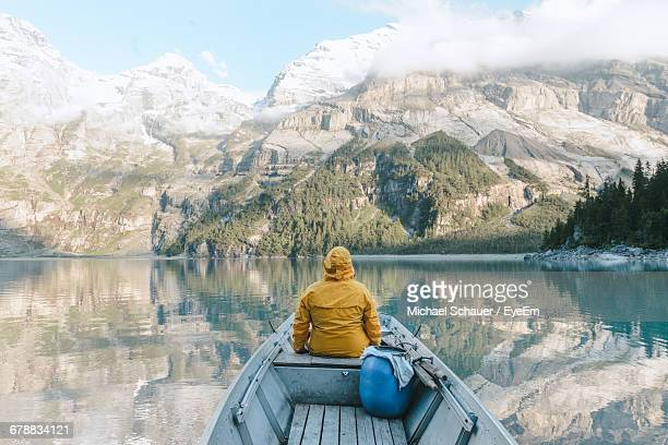 Rear View Of Person Sitting On Boat In Lake