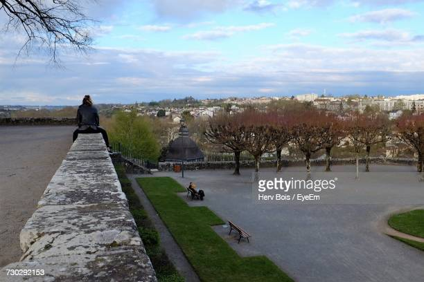 Rear View Of Person Sitting On Wall By Park Against Sky