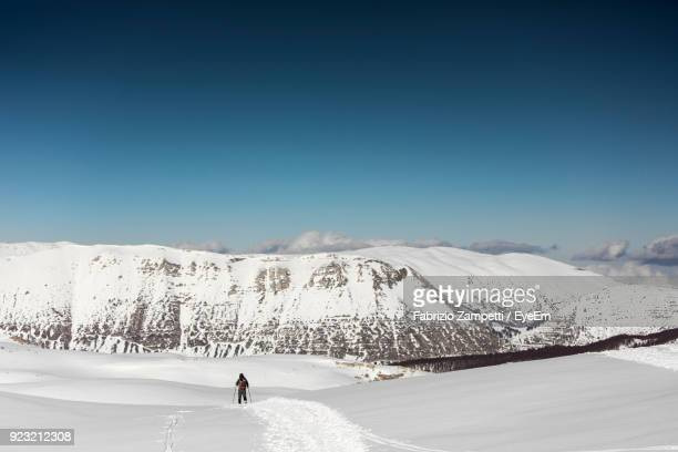 rear view of person skiing on snowcapped mountain against sky - fabrizio zampetti foto e immagini stock