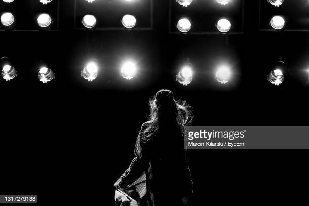 rear view of person standing against illuminated lights at night - catwalk stock pictures, royalty-free photos & images