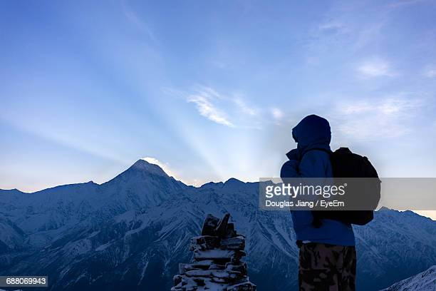 Rear View Of Person Standing Against Snowcapped Mountain