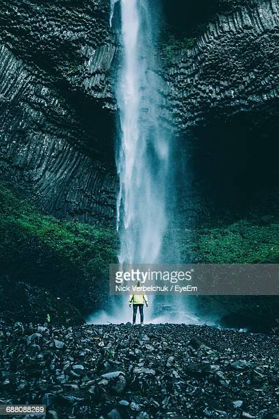 Rear View Of Person Standing Against Waterfall