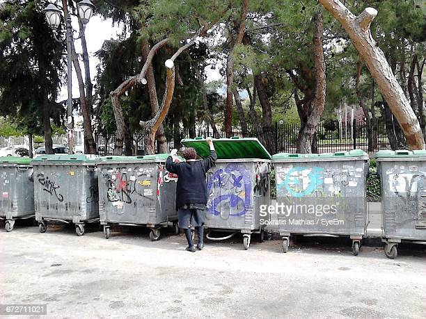 Rear View Of Person Standing By Garbage Bins Against Trees