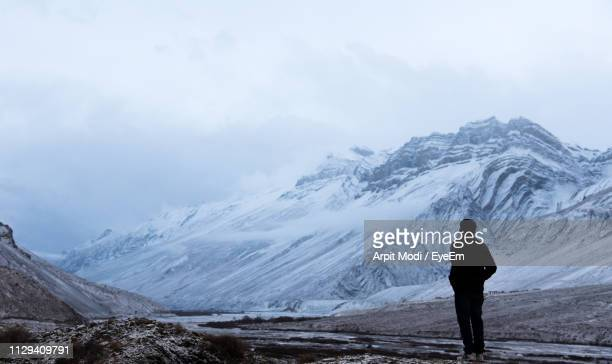 rear view of person standing by snowcapped mountain against sky - shimla stock pictures, royalty-free photos & images