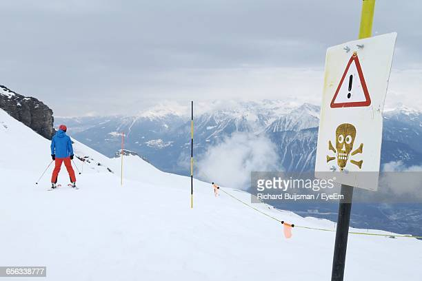 Rear View Of Person Standing Next To Danger Sign Board Against Cloudy Sky