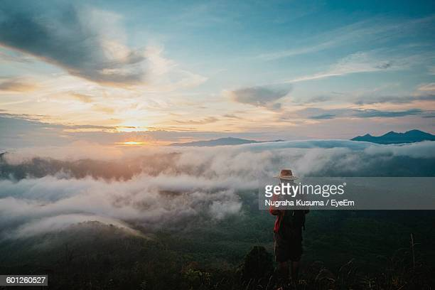 Rear View Of Person Standing On Landscape Against Sky During Sunrise