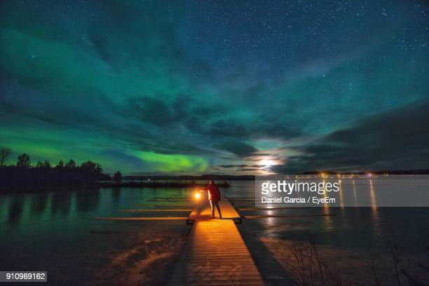 Rear View Of Person Standing On Pier Over Lake At Night