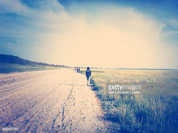 rear view of person standing on road amidst grassy field against sky - le crotoy photos et images de collection
