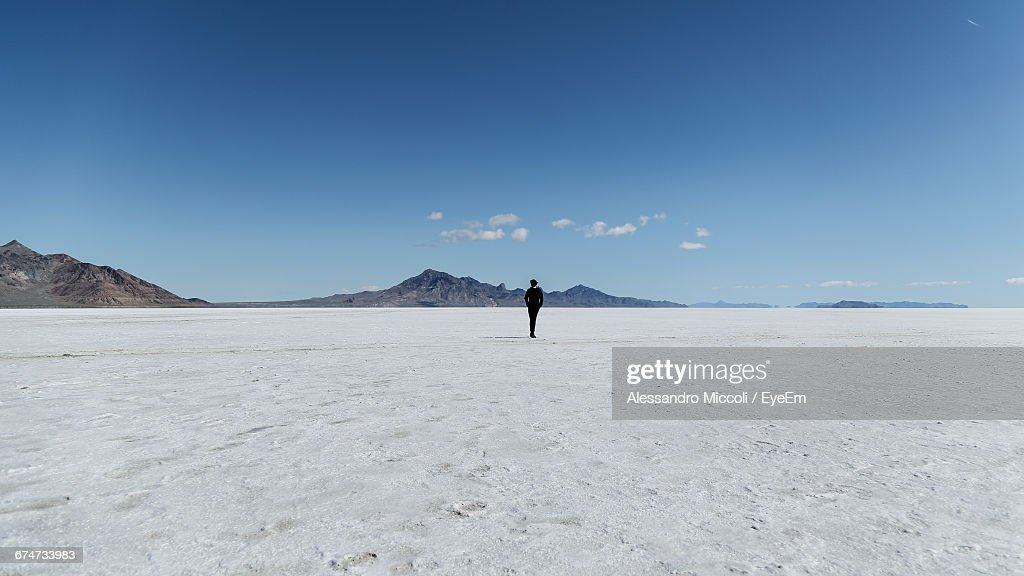 Rear View Of Person Standing On Salt Flat Against Sky : Stock Photo