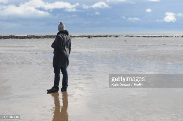 Rear View Of Person Standing On Shore At Beach Against Sky