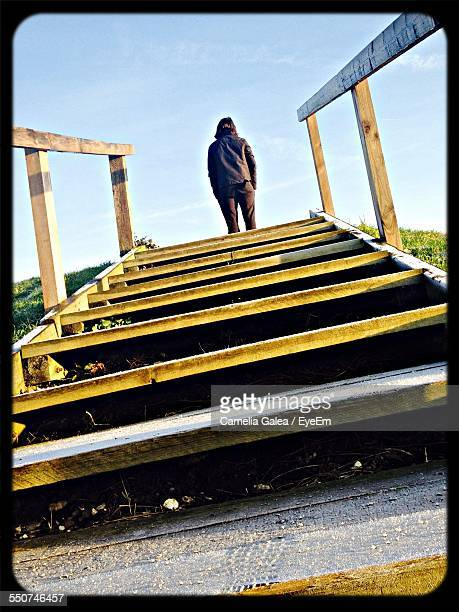 rear view of person standing on steps against sky - gillingham stock pictures, royalty-free photos & images