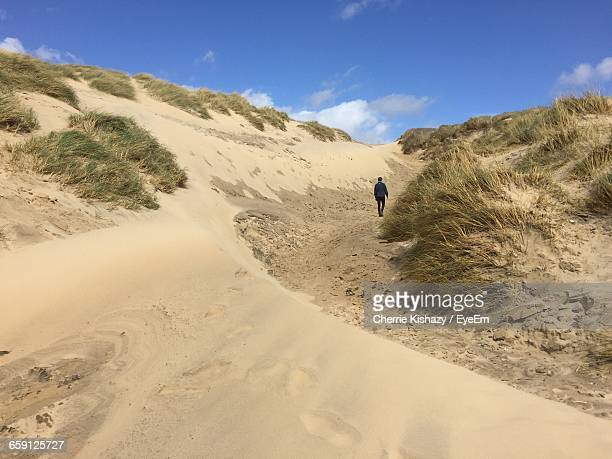 rear view of person walking at camber sands beach - camber sands stock photos and pictures
