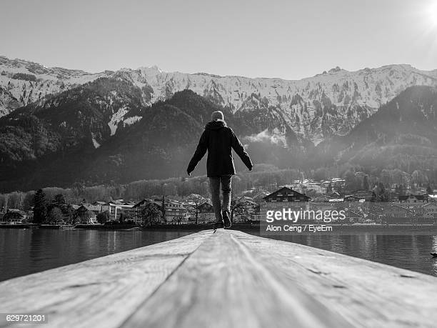 Rear View Of Person Walking On Pier Over Lake Against Mountains