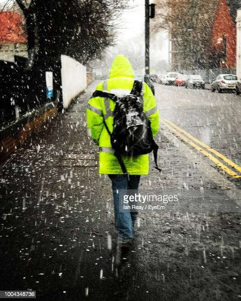 rear view of person walking on road during rainy season - torrential rain stock pictures, royalty-free photos & images