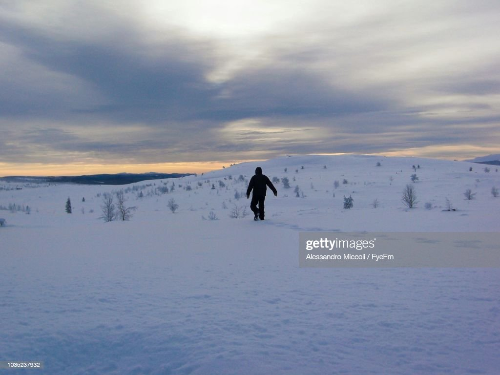 Rear View Of Person Walking On Snow Covered Field Against Cloudy Sky : Stock Photo