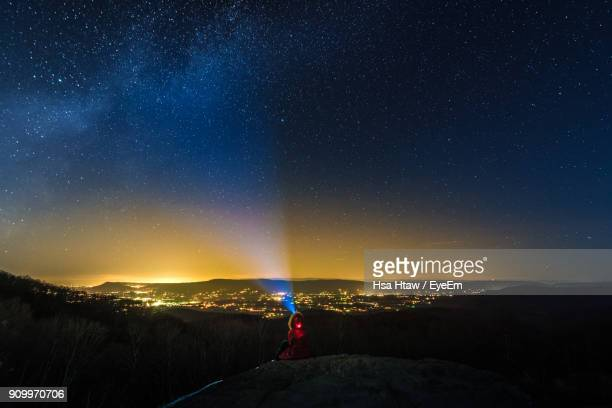 Rear View Of Person With Flashlight Against Star Field