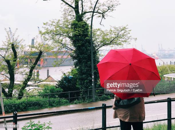 Rear View Of Person With Red Umbrella Standing Against River During Rainy Season