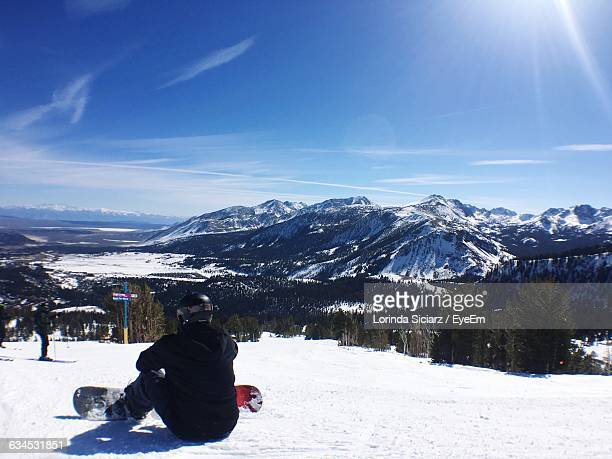 Rear View Of Person With Snowboard Relaxing On Snowcapped Mountains