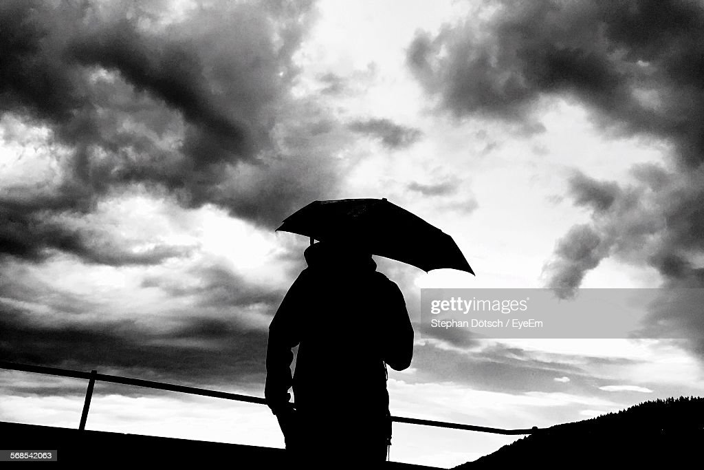Rear View Of Person With Umbrella Standing Against Cloudy Sky : Stock Photo